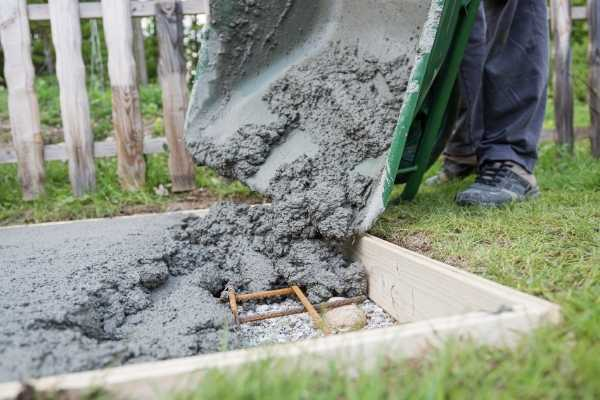worker pouring cement for backyard cement pad